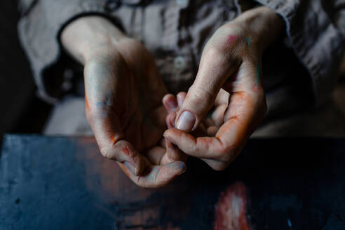 Close-up of painted hands of a female painter in her studio - OGF00103