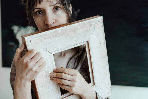 Portrait of a female painter in her studio holding picture frame - OGF00112
