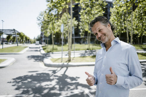 Portrait of smiling mature man with thumbs up - KNSF06137