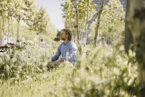 Young man meditating in urban park - KNSF06155