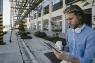 Young man using tablet in the city - KNSF06167