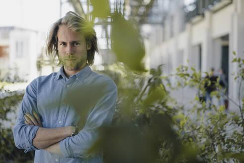 Portrait of a confident young man behind a plant - KNSF06176