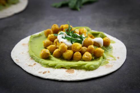 Pita-Brot mit Avocado-Creme, Kurkuma-Kichererbsen, Joghurt-Sauce und Petersilie - LVF08228