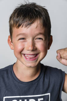 Portrait of strong boy, laughing, white background - MGIF00655