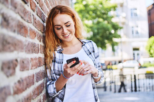 Young woman leaning against brick wall in the city while using smartphone - BSZF01317