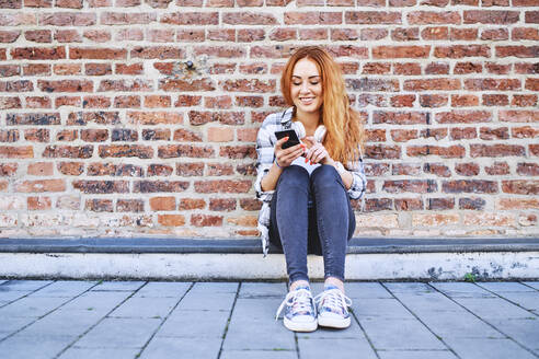 Smiling young woman sitting outdoors in the city and using smartphone - BSZF01326
