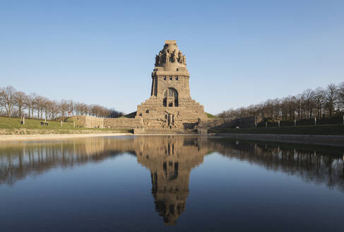 Lake of tears with reflection of Völkerschlachtdenkmal against clear blue sky, Saxony, Germany - GWF06201