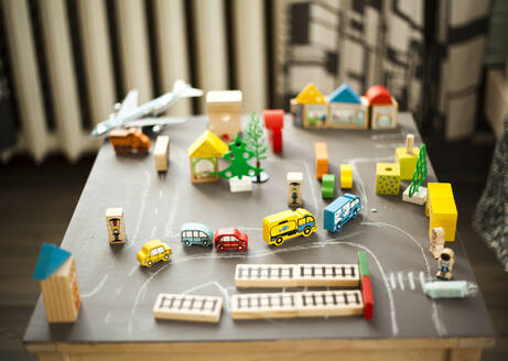 Wooden buildings and car toys on table - BLEF13459