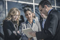 Business people using digital tablet outside office - BLEF13531
