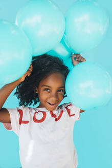Little girl In front of a blue wall, holding balloons - JCMF00087