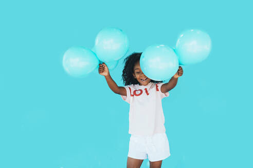 Little girl In front of a blue wall, holding balloons - JCMF00090