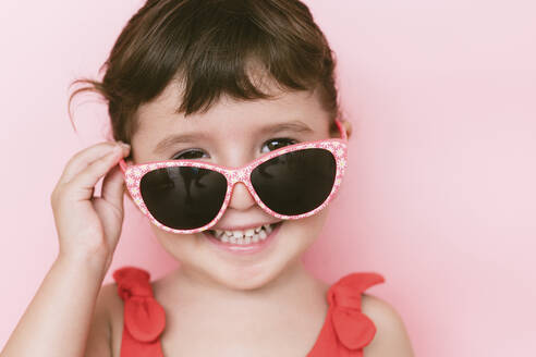 Portrait of happy little girl wearing sunglasses against pink background - GEMF03036