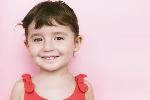 Portrait of smiling little girl in front of pink background - GEMF03039