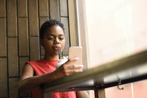 Portrait of young woman in a bar looking at cell phone - JSMF01203