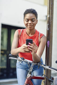 Portrait of smiling young woman leaning on handle bar of bicycle looking at cell phone - JSMF01206