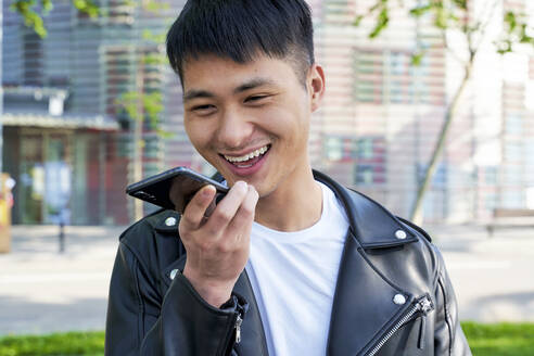 Happy young man sending a voice message with cell phone, Barcelona, Spain - GEMF03055