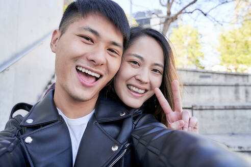 Portrait of happy young couple making victory sign - GEMF03097