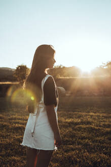 Young woman standing in field landscape at sunset - ACPF00573