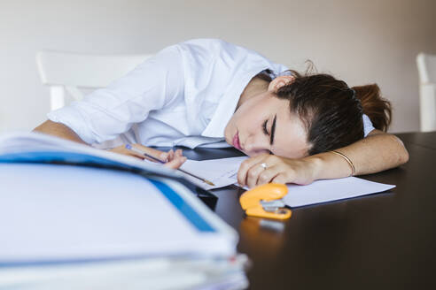 Exhausted female student lying on desk at home with documents - LJF00594