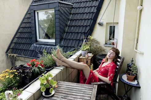 Deutschland,NRW,Ruhrgebiet,Stadt Essen,Junge Frau im roten Kleid auf dem Balkon - FLLF00256