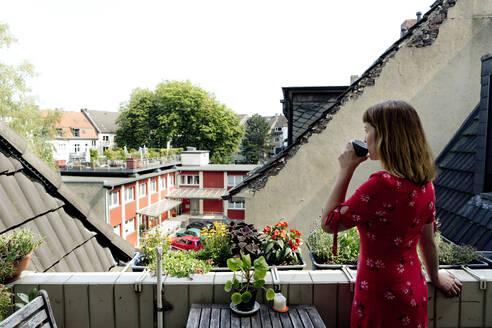 Deutschland,NRW,Ruhrgebiet,Stadt Essen,Junge Frau im roten Kleid auf dem Balkon - FLLF00259