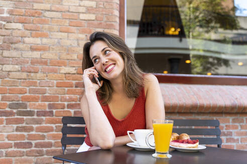 Portrait of smiling young woman on the phone sitting at street cafe - AFVF03626