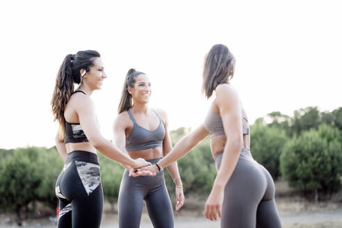 Three happy sporty women stacking their hands after doing sports - OCMF00559