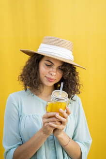Portrait of woman with straw hat, drinking juice, yellow background - AFVF03664