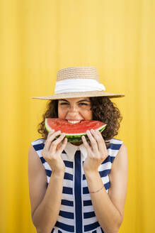 Portrait of woman eating watermelon, yellow background - AFVF03667