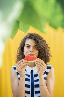 Portrait of woman eating watermelon, yellow background - AFVF03670