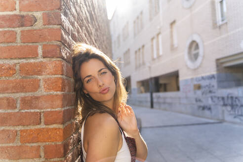 Young woman leaning on brick wall and looking at camera - AFVF03703