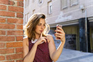 Young woman leaning on brick wall, taking a selfie - AFVF03709