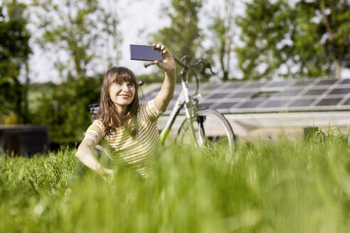 Relaxed woman sitting on a meadow with bicycle taking a selfie - FMKF05773