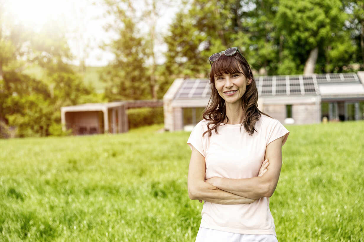 Portrait of smiling woman standing on meadow in front of a house - FMKF05788 - Jo Kirchherr/Westend61