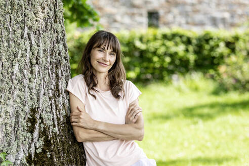 Portrait of confident brunette woman leaning against a tree trunk - FMKF05800
