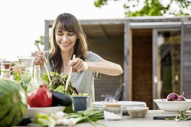 Smiling woman preparing a salad on garden table - FMKF05806