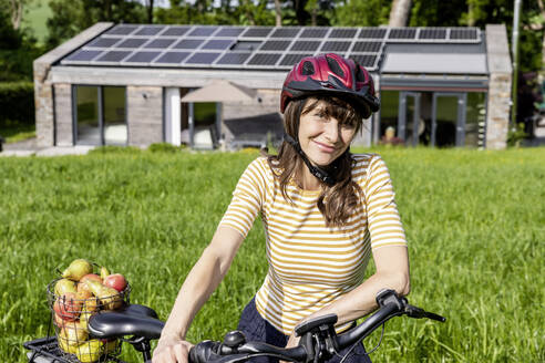 Portrait of smiling woman with bicycle and organic fruit on a meadow in front of a house - FMKF05824