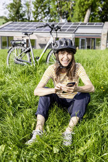 Laughing woman with bicycle using cell phone on a meadow in front of a house - FMKF05830