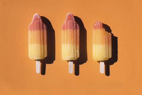 Directly above shot of sorbets arranged on orange background - MOMF00739