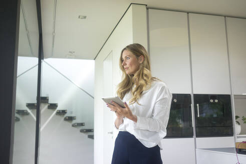 Businesswoman holding tablet in modern home - MOEF02396