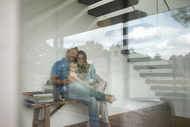 Happy family of three sitting on a bench behind windowpane at home - MOEF02399