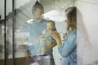 Happy family of three standing behind the window at home - MOEF02417