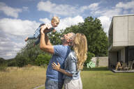 Happy father with mother lifting up baby girl in garden - MOEF02423