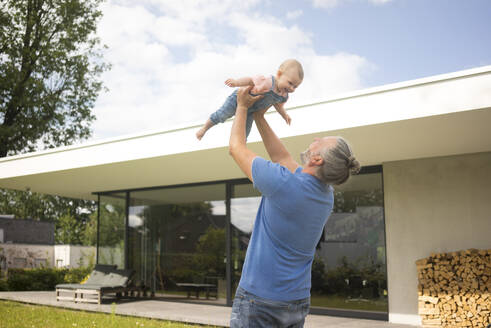 Happy mature man lifting up baby girl in garden of his house - MOEF02432