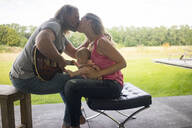 Man with guitar kissing woman with baby girl sitting on her lap - MOEF02441
