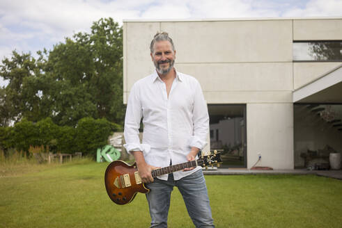 Portrait of mature man standing on lawn in front of his house holding guitar - MOEF02444
