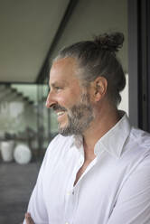 Portrait of happy mature man with hair bun - MOEF02447