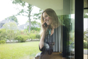 Smiling woman talking on the phone behind windowpane at home - MOEF02456