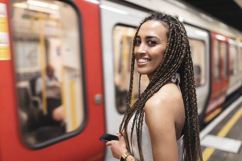 Portrait of happy young woman waiting at subway station platform, London, UK - WPEF01695