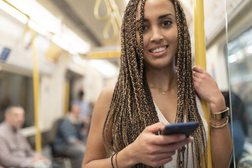 Portrait of smiling young woman with cell phone in underground train, London, UK - WPEF01698